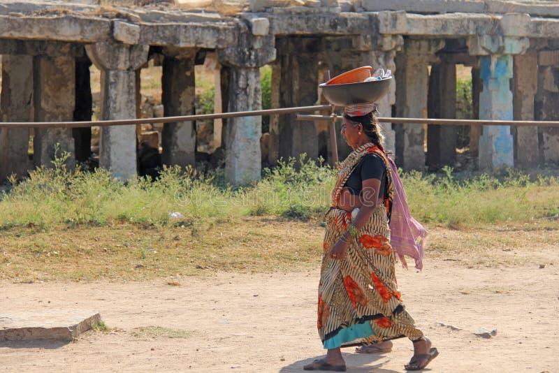 Indien, Hampi, am 2. Februar 2018 Eine indische Frau in einem Sari trägt eine schwere Last auf ihrem Kopf Weibliche Arbeit in Ind lizenzfreies stockfoto