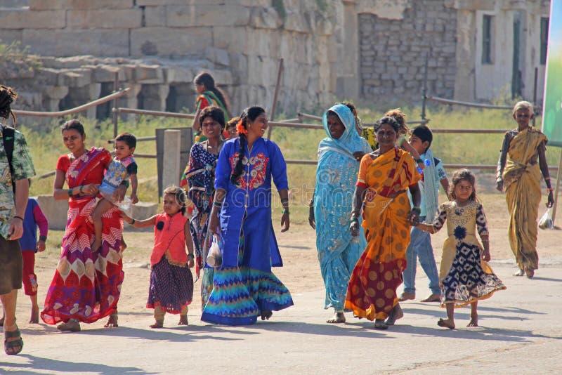 Indien Hampi, 02 Februari 2018 Den huvudsakliga gatan av den Hampi byn är kvinnor i ljusa och färgrika sari, män, barn, en grupp  royaltyfri fotografi