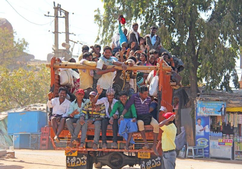 Indien Hampi, 02 Februari 2018 En härlig indisk lastbil bär mycket indiska personer Det glade Hindus leendet och att vinka deras royaltyfri bild