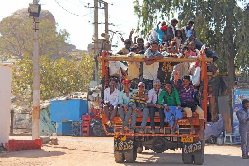 Indien Hampi, 02 Februari 2018 En härlig indisk lastbil bär mycket indiska personer Det glade Hindus leendet och att vinka deras royaltyfria bilder