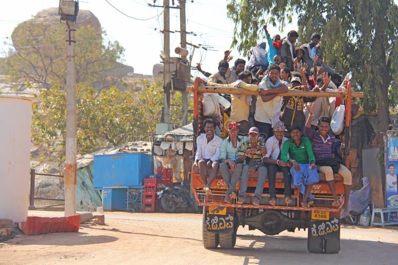 Indien Hampi, 02 Februari 2018 En härlig indisk lastbil bär mycket indiska personer Det glade Hindus leendet och att vinka deras royaltyfri foto