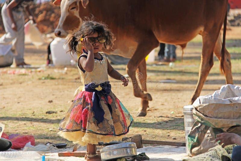 Indien Hampi, 02 Februari 2018 En liten fattig och smutsig indisk flicka som spelar med solglasögon Lite flicka i stora exponerin royaltyfri foto