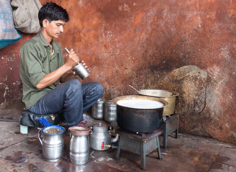 Indien man som förbereder den söta masalaen chai i mitt på streen fotografering för bildbyråer