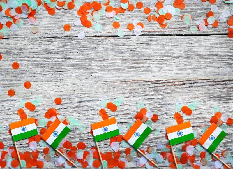 Indien-Unabhängigkeitstag am 15. August, Indien-Miniflaggen mit Konfettis drei Farben grünes Orange und weiß, auf weißem rustikal stockbilder