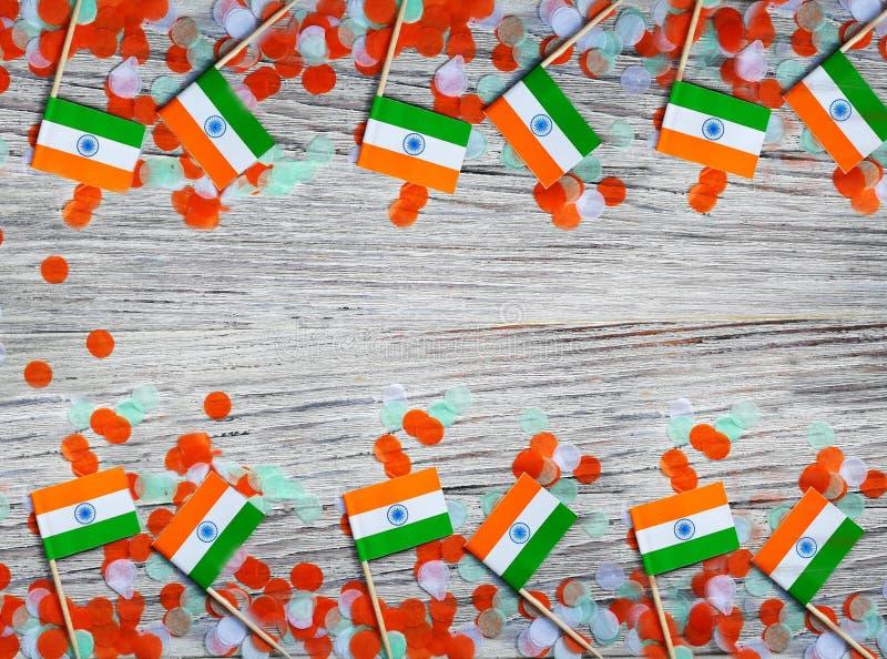 Indien-Unabhängigkeitstag am 15. August, Indien-Miniflaggen mit Konfettis drei Farben grünes Orange und weiß, auf weißem rustikal stockfotografie