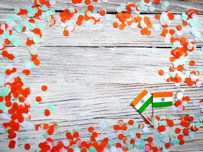 Indien-Unabhängigkeitstag am 15. August, zwei Mini-Indien-Flaggen mit Konfettis drei Farben grünes Orange und weiß, auf weißem stockfotografie