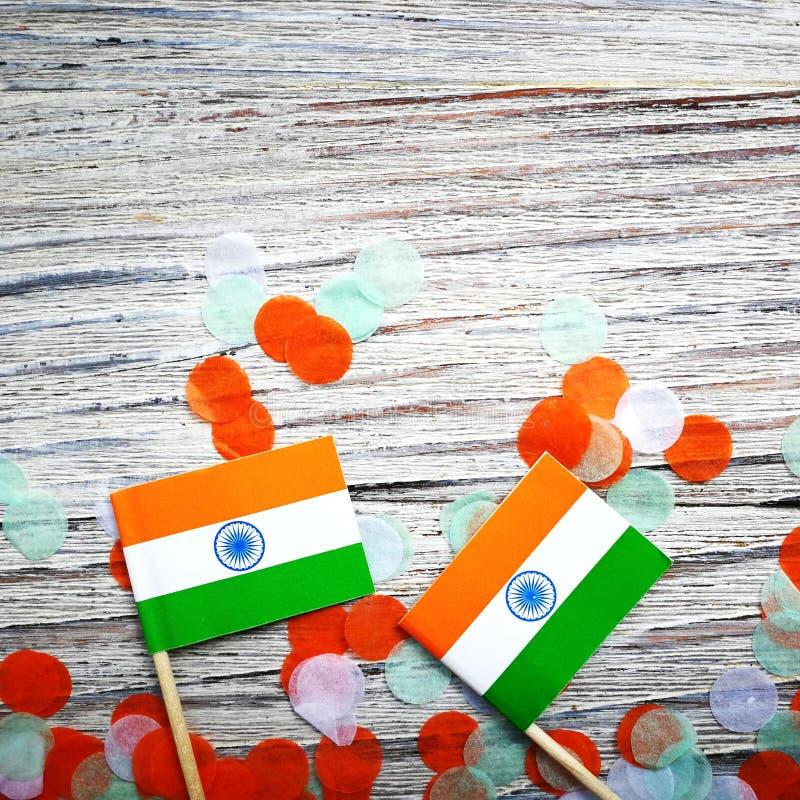 Indien-Unabhängigkeitstag am 15. August, zwei Mini-Indien-Flaggen mit Konfettis drei Farben grünes Orange und weiß, auf weißem stockbilder