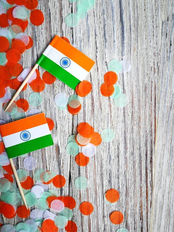 Indien-Unabhängigkeitstag am 15. August, zwei Mini-Indien-Flaggen mit Konfettis drei Farben grünes Orange und weiß, auf weißem stockbild