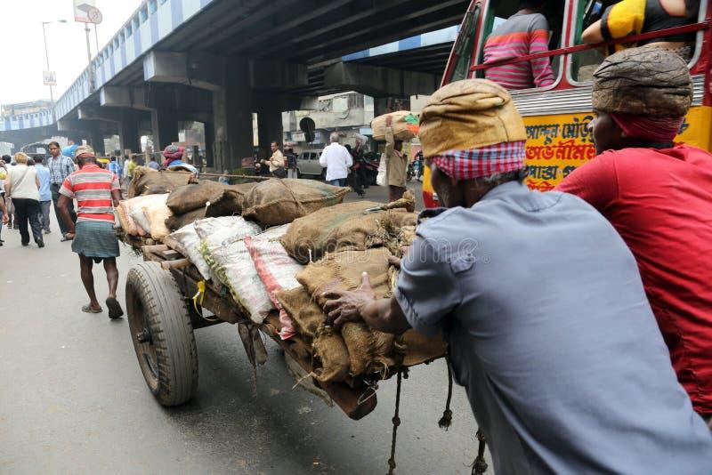 Indiens travaillants durs poussant la charge lourde par des rues de Kolkata images libres de droits