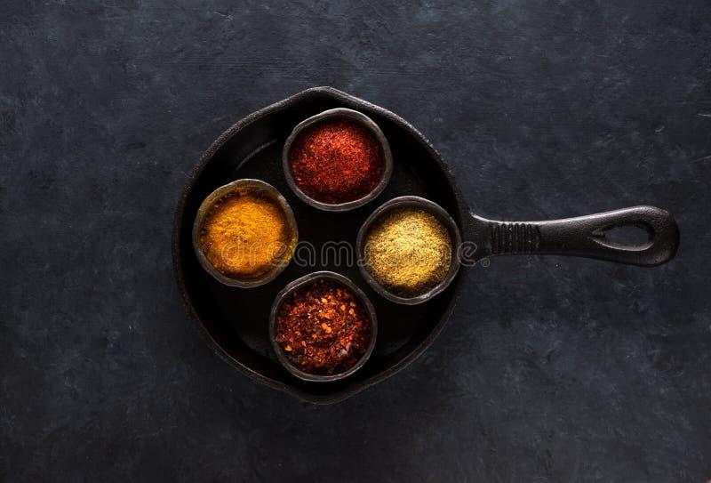 Indierkryddor och kryddigt i bunkar i en gjutjärnpanna på svärtar konkret bakgrund, bästa sikt royaltyfri foto