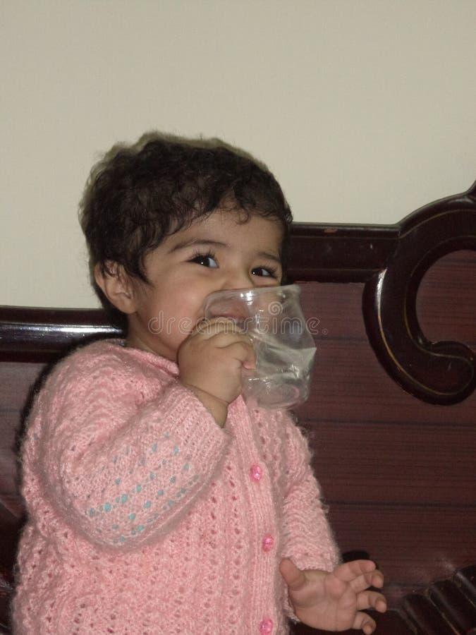 Indiern behandla som ett barn krossande plast- vattenexponeringsglas för flickan royaltyfri fotografi