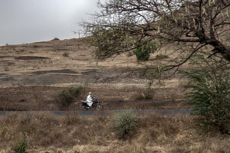 Indiern vallfärdar i vit kläder som rider en motorcykel royaltyfri bild