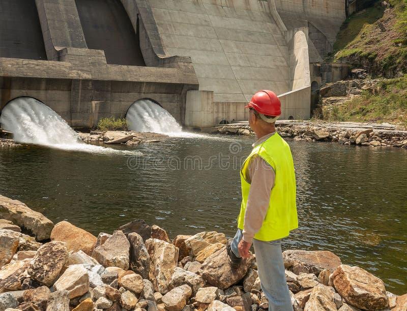 Indietro del lavoratore in un casco contro il contesto delle turbine idroelettriche immagine stock