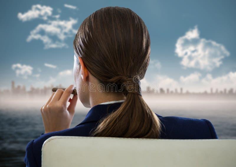 Indietro del sigaro di fumo messo della donna di affari e di esame orizzonte confuso e dell'acqua immagini stock libere da diritti