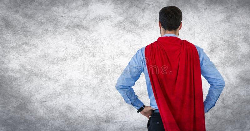Indietro del supereroe dell'uomo di affari con le mani sulle anche contro fondo e la sovrapposizione bianchi di lerciume fotografie stock libere da diritti