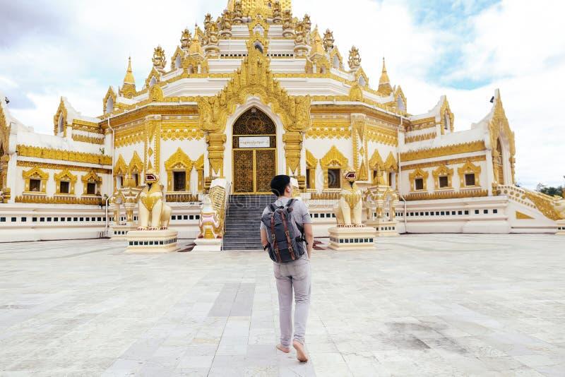 Indietro del viaggiatore con zaino e sacco a pelo del giovane che cammina verso il nome birmano del tempio immagine stock