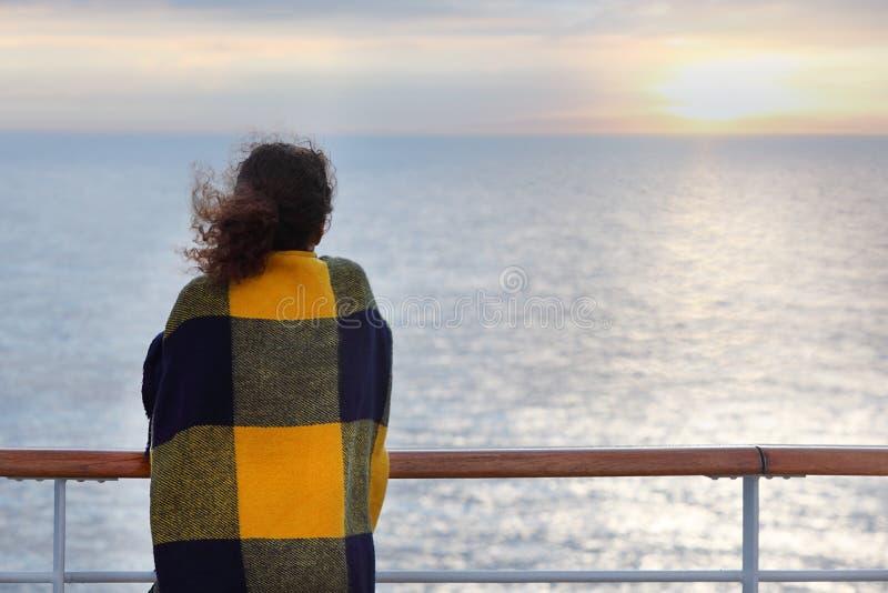 Indietro della donna che si leva in piedi sulla piattaforma della fodera di crociera immagini stock