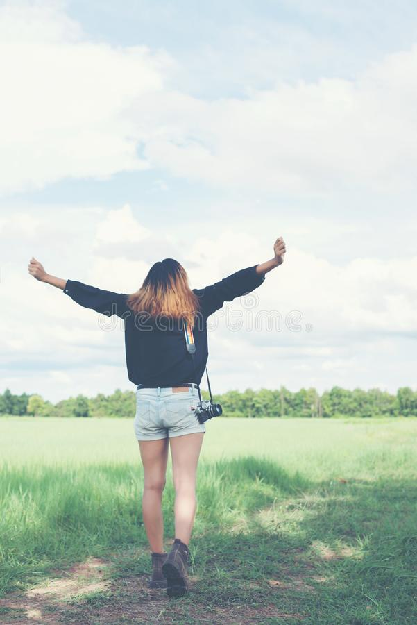 Indietro della giovane donna che porta la retro macchina fotografica nel campo di erba goda della t immagini stock