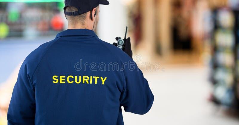 Indietro della guardia giurata con il walkie-talkie contro il centro commerciale confuso fotografia stock libera da diritti