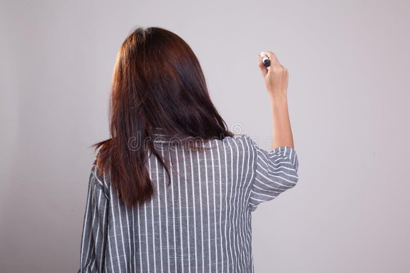 Indietro della ragazza asiatica scriva nell'aria con una penna di indicatore immagini stock libere da diritti