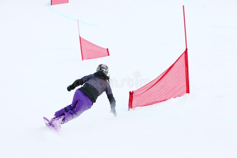 Indietro dello snowboard di guida della giovane donna immagini stock