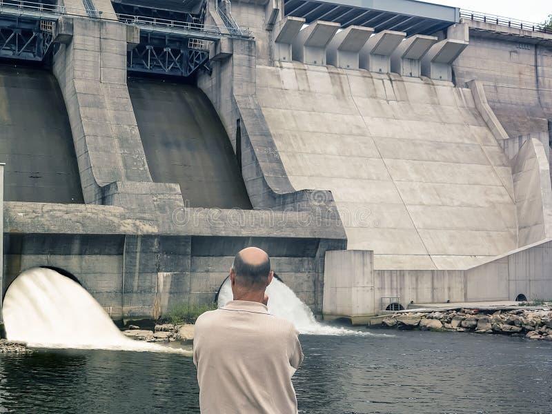 Indietro di un uomo che esamina diga e le turbine di una centrale idroelettrica con gli scorrimenti dell'acqua di caduta fotografia stock