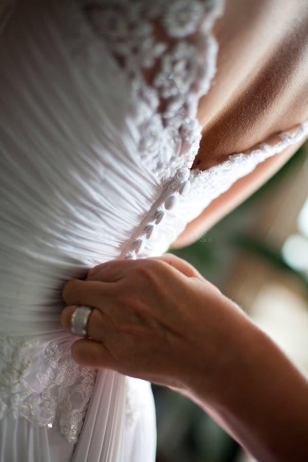 Indietro di un vestito da cerimonia nuziale che è abbottonato fotografia stock libera da diritti