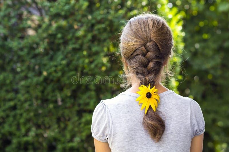 Indietro di una donna con il fiore in suoi capelli immagini stock libere da diritti