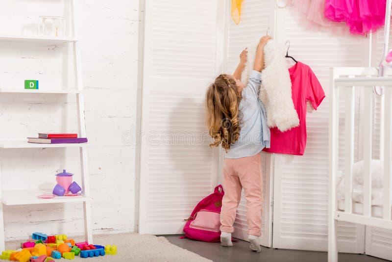 indietro punto di vista del bambino che prende i ganci con i vestiti dallo schermo piegante immagini stock