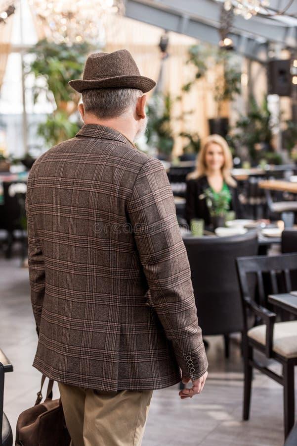indietro punto di vista dell'uomo in cappello e rivestimento alla moda con la donna che si siede alla tavola immagine stock libera da diritti