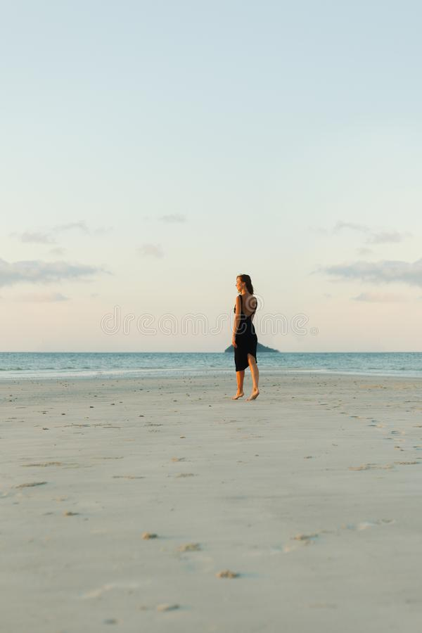 indietro punto di vista della donna che cammina sulla spiaggia sabbiosa in vestito immagini stock