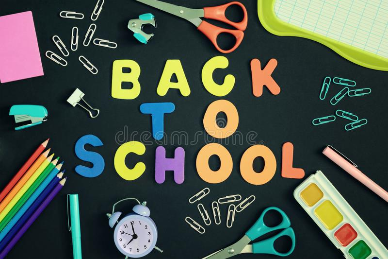 Indietro sui precedenti neri con le lettere colorate variopinte di nuovo alla scuola Intorno alla cancelleria, un'immagine lumino immagini stock libere da diritti