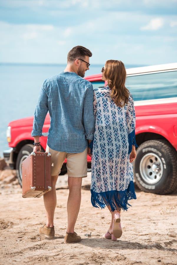 indietro vista delle coppie con la valigia che va a fotografia stock libera da diritti