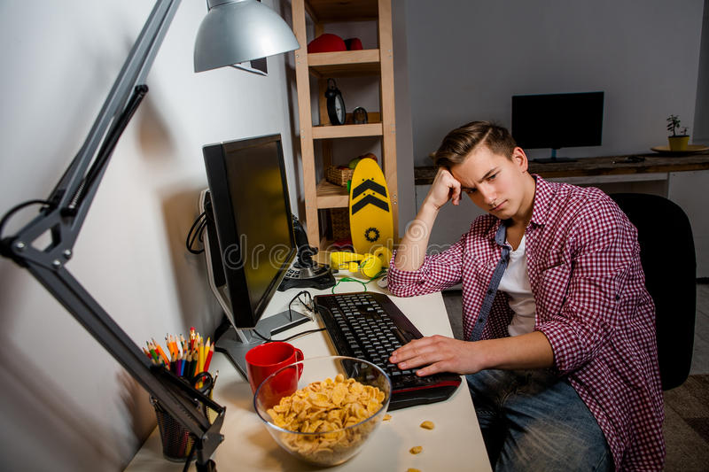 Indifferent teenage boy sitting at the table in his room. royalty free stock image