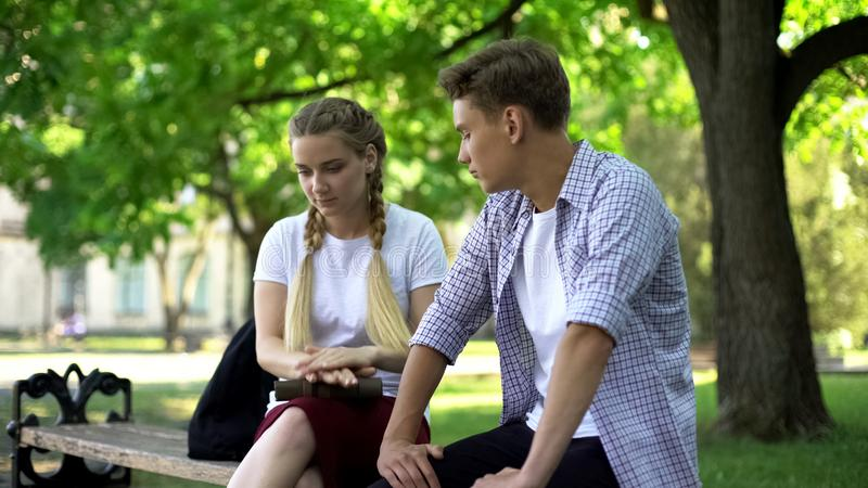 Indifferent teens sitting on bench, bad blind date, wasting time, ignoring. Stock photo stock image