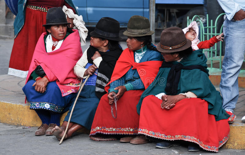 Indigence Ecuadorian women. Indigence Peruvian women with traditional outfits sitting on the floor stock image