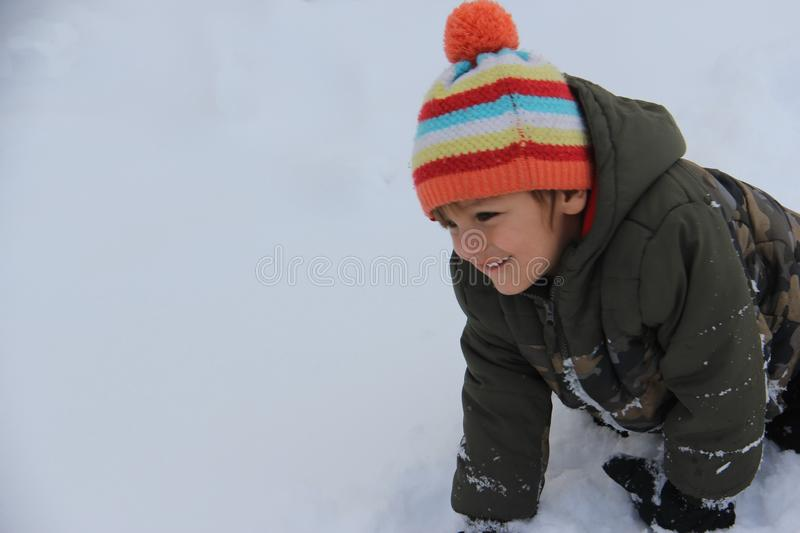Indigenous boy having Winter snow fun in the prairie. Indigenous, First Nations boy playing in the snow on the Canadian prairies. Fun in the snow, mother eand royalty free stock photography