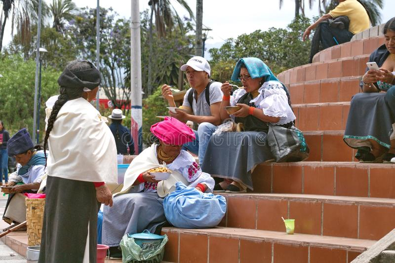 People sitting on steps in Cotacachi. Indigenous people sitting on the steps of the church on Day of the Dead in Cotacachi, Ecuador royalty free stock image