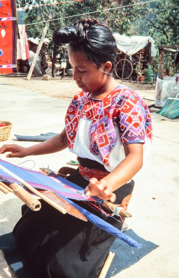 Indigenous Tzotzil maya woman weaving a traditional Huipil at the loom. royalty free stock images
