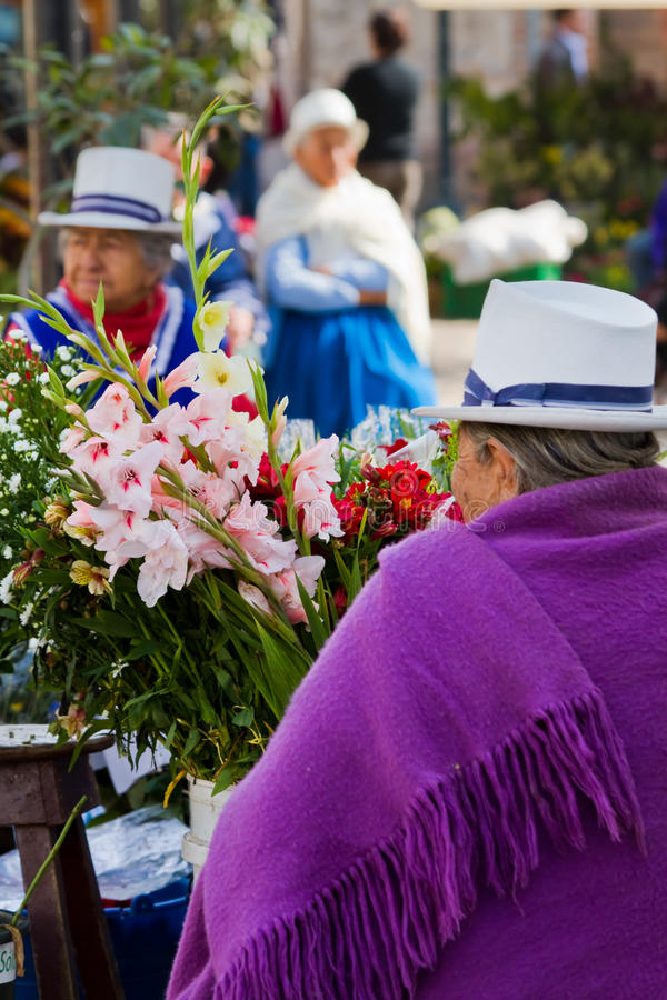 Indigenous woman selling flowers in Plaza de. CUENCA, ECUADOR - AUGUST 22, 2010: Indigenous woman selling flowers in Plaza de Flores Square in Cuenca royalty free stock images