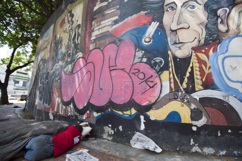 Indigente che dorme sul pavimento con i graffiti di Simon Bolivar, Cara fotografie stock