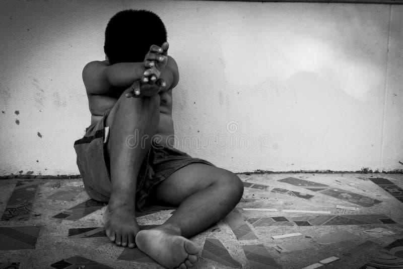 Indigente del bambino che si siede contro il muro di cemento immagine stock