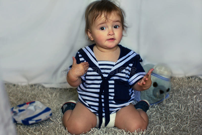 Indignant baby girl in the nautical striped vest sits on the car stock photography