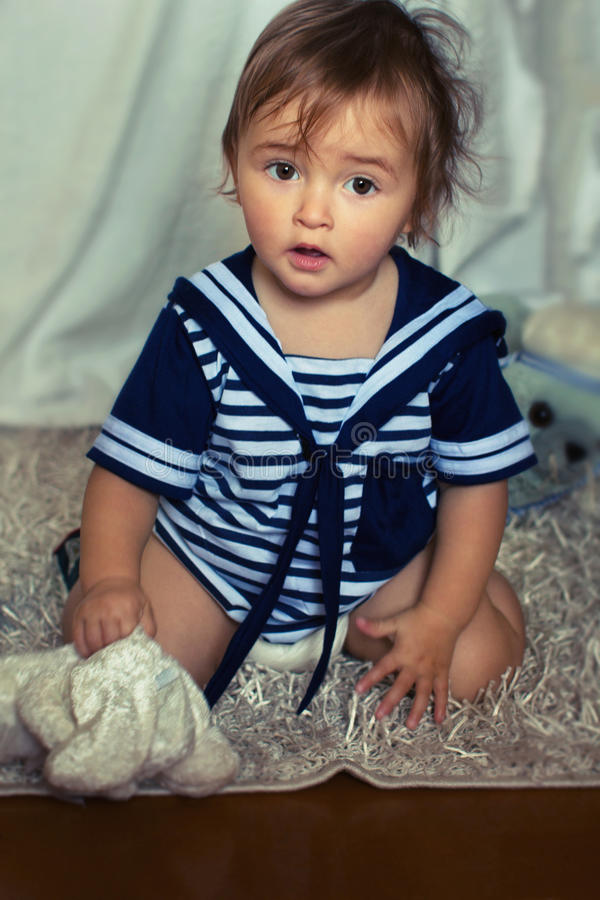 Indignant baby girl in the nautical striped vest sits stock photo