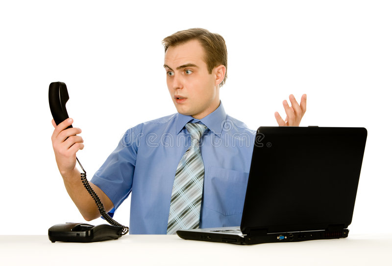 Indignant man working on laptop. Isolated on whi stock photo