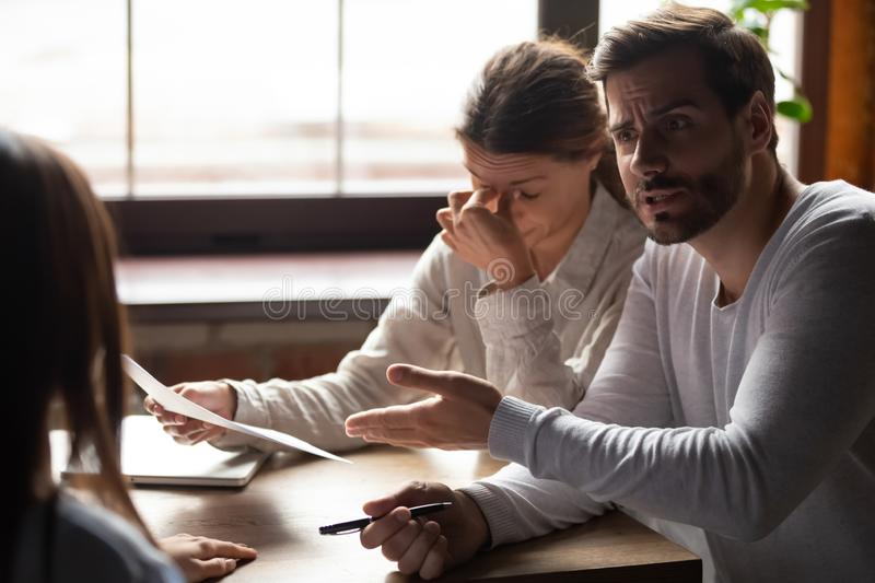 Indignant millennial male accusing incompetent female colleague. Diverse millennial people sitting at table in office indignant men accusing incompetent stock image