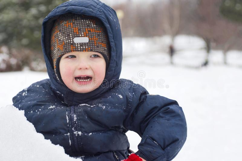Indignant, unhappy small child walks in winter outdoors royalty free stock images