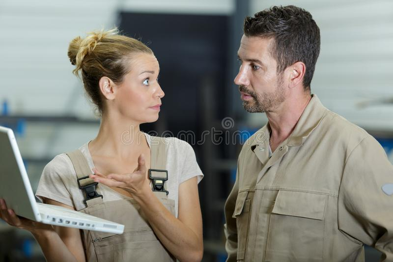 Indignant worker showing laptop screen to colleague stock images
