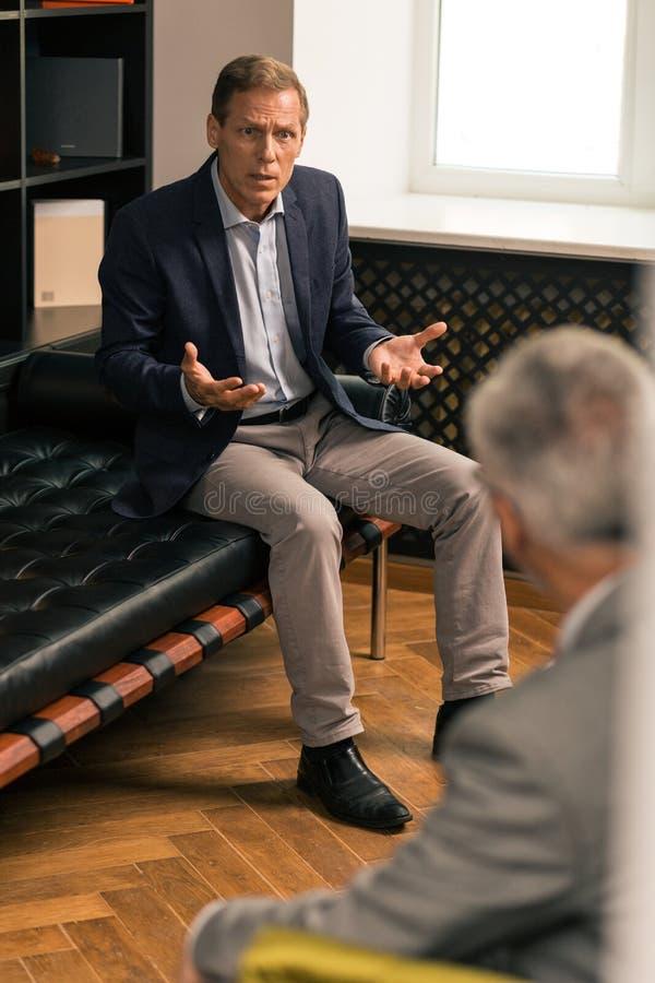 Indignerad medelålders Caucasian man som sitter på soffan arkivbilder