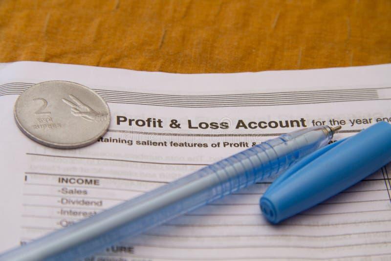 Indin-Rupienmünze und -stift auf Gewinn- und Verlustkonto stockfoto